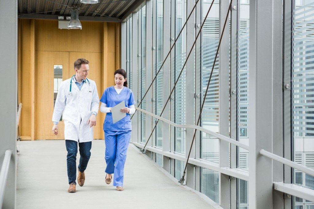 a doctor and nurse walking on the the hospital's hallway