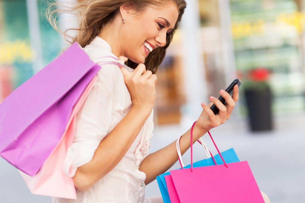 Woman holding shopping bags while looking at phone