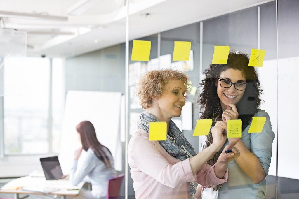 Employees posting sticky notes on glass wall