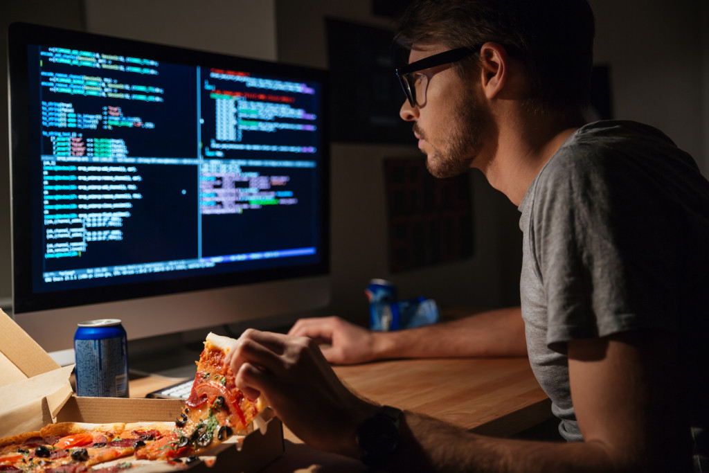man coding and eating pizza